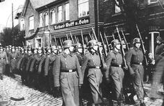 SS guards from the concentration camp , march through Neuengamme . Photograph taken on 9 Nov 1942