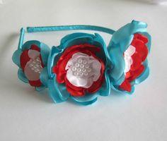 Tiara plástica fina forrada com fita de cetim, com três flores de diferentes tamanhos azul piscina, vermelho e branco.