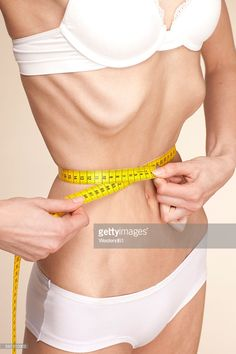 Stock Photo : Anorexic young woman measuring her waist