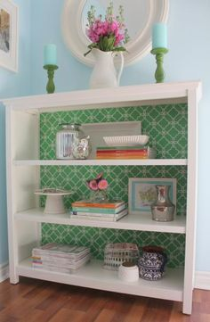 lining the back of a bookshelf with pretty wall paper.