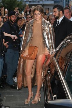 Arm candy: She carried her runway show essentials in a brown leather satchel...