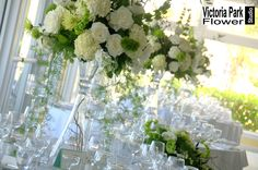 Beautifully tall centerpieces designed with White Hydrangea, Stock and Roses with Green Dianthus, Fuji Mums, Bells of Ireland and Curly Willow