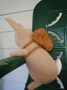 Basket Bunnies are knit in one piece from the bottom up to the tip of the ears. Arms, feet, and tail are knitted separately and seamed on. A little basket knit in simple basket-weave stitch with i-cord straps wraps around each of the bunny's arms. Finished bunny is about 11 inches tall.