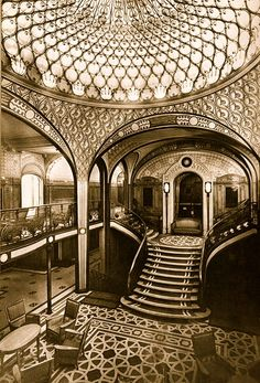 The incredible grand staircase of the French Lines, SS Paris. Beautiful lobby with natural light flowing through the domed skylight.