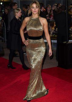 Ralph Lauren.Jennifer Lawrence-De nuevo con un look oro, con un vestido halter con una cinta negra en la cintura y un efecto de piel de cocodrilo, de Ralph Lauren.