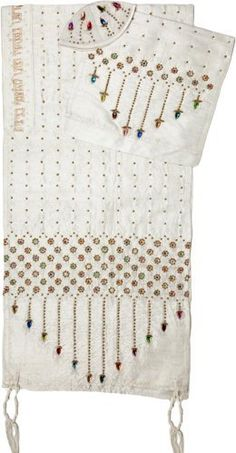 White Silk Tallit with Flowers, Rhinestones and Hebrew Text by World of Judaica. $368.00. This white silk Tallit features colorful rhinestones and flowers on the sides and Hebrew text in a traditional font embroidered in gold thread at the top. This incredible white silk Tallit features red, yellow, green, orange, purple and blue stones on the sides at the atop dotted lines and in the center of flowers. This Tallit has pre-tied Tzitzit strings on the corners that ar...