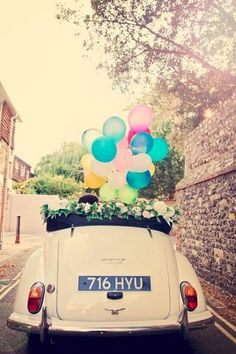cream vintage wedding car with colorful balloons is so funny