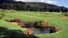 "Designed by golf legend Greg Norman and architect Ted Robinson, ""The Experience"" at Four Seasons Lana'i at Koele championship course offers stunning views of mountains and lush greens, with the ocean in the distance."