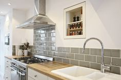 Oak worktop with sage green metro tiles