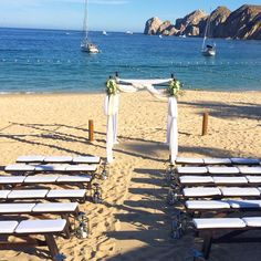 Rustic beach ceremony at the Hacienda & Cocina. Brown benches on Medano Beach Cabo.