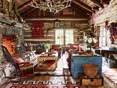 Overlooking the cabin's living room is a chandelier made with naturally shed elk antlers; beside the hearth, a woven-twig rocking chair is draped with a vintage Capps Indian-trade blanket, and an antique New Mexico pine table stands atop an early-20th-century Navajo rug.