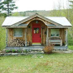 Rustic. Metal roof. Peeled log posts. Single storey, which is unusual for tiny house. I love the coloured door and arch.