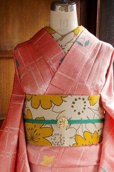 ストロベリーのシャーベットのような、パウダーがかったスモーキーな赤色の地に、光がきらめくような変わり格子とレトロなお花模様が織り出されたウールの単着物です。