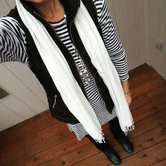A comfy and cute outfit for fall: a long striped top with leggings, a quilted vest, scarf, and boots
