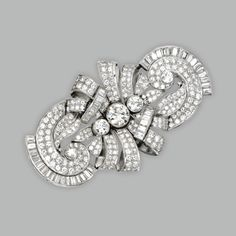 Platinum and Diamond Brooch, Circa 1935. Of scroll design set in the center with a 2.35 carat round diamond, accented by 10.75 carats of round diamonds, and 4 carats of baguette diamonds.