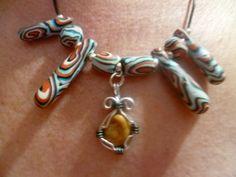 piedra de la jaqueca engastada en alambre  y montada en un collar con abalorios de arcilla polimerica