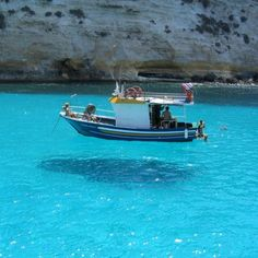 This picture is taken on One House Bay in Greece. The water is so clear that the boat seems to be floating in the air.