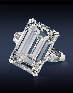 HRD Certified 18.03 Ct, H Internally Flawless Emerald Cut Diamond Flanked by 0.70 Ct Tapered Baguette Cut Diamonds (6 Stones), Mounted in Platinum and 18K White Gold.