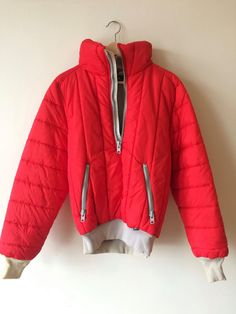 This is an awesome red puffy ski jacket, with grey ribbed collar and cuffs, half-zip up with zipped pockets. Made by Serac USA. Material: Shell: 100% Nylon Interfill: 100% Polyester  Size: Marked Size 42. Fits a Mens Small. Please check measurments. Measurements: Chest: 24 Shoulder to Shoulder (across the back): 20 Sleeve (top shoulder seam to end of cuff): 29 Length (from top of collar down the center of the back): 27  Condition: Very good. slight yellowing on some parts of the grey ribbed…