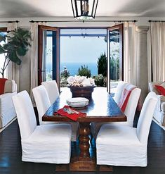 A large wooden dining room table with red linens and bright white slipcovers on chairs.