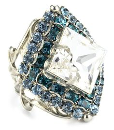 "For a dramatic look, the Sorrelli ""Salt Water"" Starburst Crystal Silver-Tone Adjustable Ring is well-suited for cocktails or a special evening occasion. Featuring a large, diamond-shaped Austrian crystal in the center, the silver-toned ring is designed with blue Austrian crystals that surround the white crystal. The bold, dramatic ring is 1 inch wide and over 1 inch long--it's bound to make a dramatic statement on your hand. The wide..."