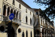 Photo taken in via San Francesco in Padua in Veneto (Italy). In the image, profile recovery from near the tomb of Antenor, you see the facades of two important historical buildings. Above the large door of the first entrance you see the large balcony with finely carved stone balustrade and the four glass doors divided by three columns. Above the roof of the building you see the deep blue of the sky with a dark green brushstrokes due to the branches of a pine.