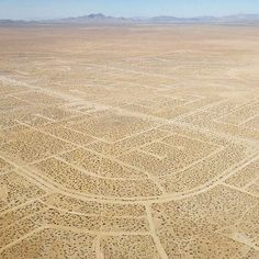 Aerial view over never finished California City. ➖ California City had its origins in 1958 when real estate developer and sociology professor Nat Mendelsohn purchased 80,000 acres (320 km2) of Mojave Desert land with the aim of master-planning California's next great city. He designed his model city, which he hoped would one day rival Los Angeles in size, around a Central Park with a 26-acre (11 ha) artificial lake. Growth fell well short of his expectations. Today, a vast grid of crumbling…