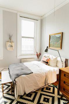 neutral bedding, patterned rug, grey walls
