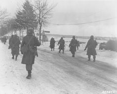 101st Airborne troops move out of Bastogne, after having been besieged there for ten days, to drive the enemy out of the surrounding district. Belgium 31 dec 1944.