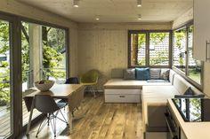 Dřevěný interiér doplňují barevné židle, stolečky a křesílka.