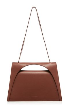 As bold and architectural as his ready-to-wear, this **J.W. Anderson** bag features an architectural foldover flap crafted in calf leather.