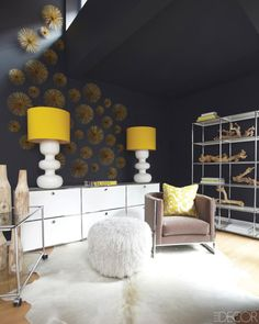 love the pouf, modular shelving, lamps and the metal wall peices (global views, i think)    USM Modular Furniture Haller Serving Cart, Credenza and Shelving Unit; Farrow & Ball paint in Off Black; Chair, Lamps, Hide Rug, Ottoman, Pillow, and Wood Bottles from Pieces.