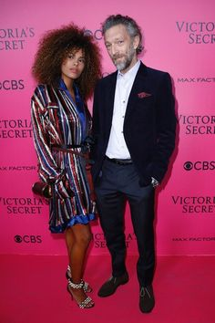 French actor Vincent Cassel (R) and his partner Tina Kunakey pose on the pink carpet upon their arrival for the 2016 Victoria's Secret Fashion Show at the Grand Palaisin Paris on November 30, 2016. / AFP / Patrick KOVARIK / RESTRICTED TO EDITORIAL USE