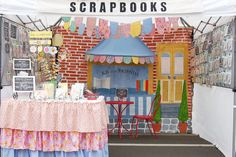 KB and Friends scrapbooking craft fair booth, with bistro table, awning and handpainted mural to create an outdoor scene.