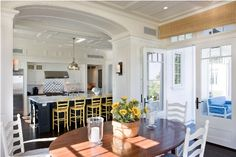 An open kitchen that flows into the dining and living areas definitely has a coastal feel to it. The white beadboard on the walls and sunny yellow accents give this upscale kitchen cottage charm.