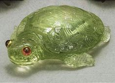 A Faberge hardstone carving of a tortoise, St. Petersburg, circa 1900 the small creature carved in pale green hardstone, probably beryl, the cabochon ruby eyes set in gold. Contained in original fitted red leather case. length 1 1/2 in. (3.8cm.)