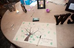 Finger print tree guest book. I really like this idea, except I'd want to make it bigger! Much bigger. Huge tree on a huge sheet of paper or fabric, big enough to fit at least 250 guests on one tree and have them sign their names by their finger print. Something much cooler to keep around afterwards also! Offbeat Bride
