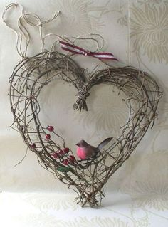 Bezaubernd: Ein einfaches Herz aus Ästen und einem mittig platziertem Vogel und ein paar Beeren.