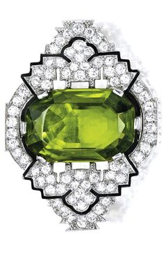 AN ART DECO PLATINUM, PERIDOT, DIAMOND & ENAMEL BROOCH. Centered by a cushion-cut peridot weighing approx 20.00 cts, within openwork surrounds set with numerous old European-cut diamonds weighing approx 3.25 cts, accented by black enamel, ca 1925.