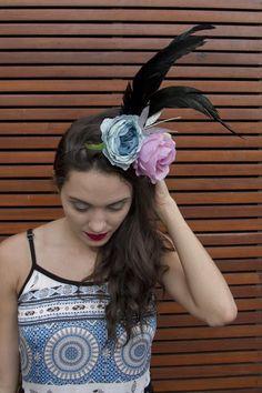 Tiara adornada com flores artificiais, penas e folhas prateadas.