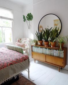 Boho bedroom in London with painted white floorboards and plants.