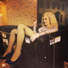 Drag queen Katya Zamolodchikova chilling in her dumpster, having a smoke