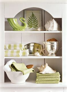 Towels are a bathroom necessity, but with clever arranging, they can also become a bathroom accessory. Show off decorative accents along with other bathroom essentials, such as soaps and lotions, for fun and functional decorating. #bathroomdecorideas #decorideas #upcycledecor #homedecor #bhg