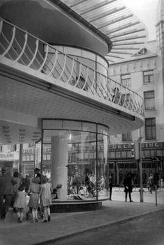 Tweede Wereldoorlog. Utrecht. Winkelend publiek bij de ingang van de Galeries Modernes - een groot warenhuis aan de Oude Gracht in Utrecht. De ronde etalages geven een goed overzicht van de geëtaleerde kleding. 10 juni 1941.