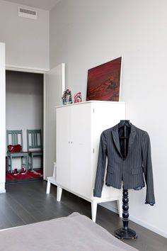 Makuuhuoneesta on kulku myös eteiseen. Valkoinen senkki ja vaateripustin ovat Hannun kirpparilöytöjä. Punainen maalaus on Marjan äidin hankinta 1970-luvulta.