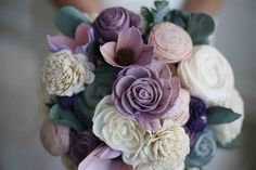 """Reminiscent of a classic English garden, this forever flower bouquet features 30 Sola Wood and pallet wood flowers and measures approximately 9 ½"""" tall accented with ferns and paper leaf accents. The stems of this bouquet are wrapped with ivory ribbon tied into a bow. Colors: White, Dusty Purple, Blush, Sage Green, Champagne Pink, Dark Purple and Ivory   Wedding items cannot be customized. Please read ourFAQS page for more information and expected production time."""