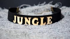 Finish off your look with this super cute JUNGLE Letter Choker necklace.Take your outfit to the next level with this black wooden choker. * Length: 30 cm * Width: 2 cm * Chain link whit lobster clasp * Letters material: wood * Band material: elastic Available in black,red and white color