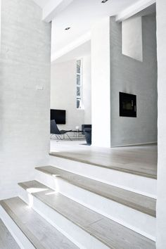 White interior - natural light, light wood or concrete stairs, white risers, textured painted white brick