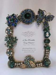 "Fabulous blue & green design. Centered with a vintage 1950's huge green rhinestone surrounded by a 2"" Juliana rhinestone wreath pin. Lisner, Weiss, & Coro earrings and brooches embellish the heavy frame. Pictures don't do this justice...it is dazzling! Holds a 4.5 x 5.75 photo; overall measures 6 x 7.5. $140"