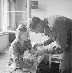 THE LIBERATION OF BERGEN-BELSEN CONCENTRATION CAMP, JUNE 1945. Father Vincent Fay, a British Army chaplain of 9th British General Hospital, christens a baby, Henji Dorochova, who was born in Belsen. The baby is held by his mother, Raissa from Voroshilovgrad in the Ukraine. During the British relief operation, new mothers were asked whether they wished their babies to be baptised and if so, under which religious denomination.